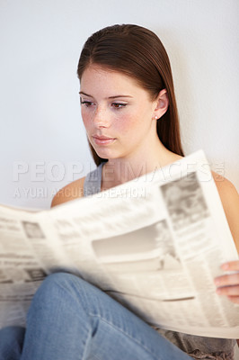 Buy stock photo A young woman reading the morning paper