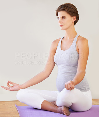 Buy stock photo A beautiful young pregnant woman meditating