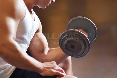 Buy stock photo Cropped shot of a muscular young man working out in the gym