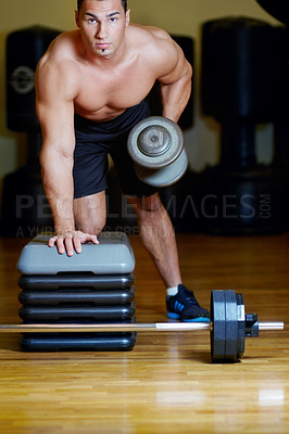 Buy stock photo A muscular young man working out in the gym