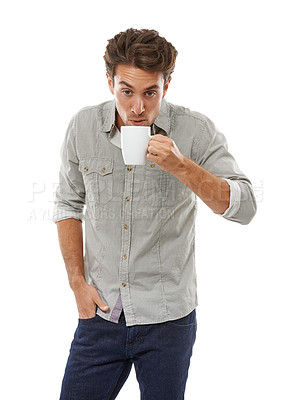 Buy stock photo A handsome young man blowing on a hot cup of coffee