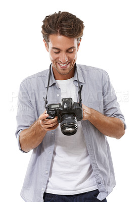 Buy stock photo A handsome young photographer checking out a picture on his camera