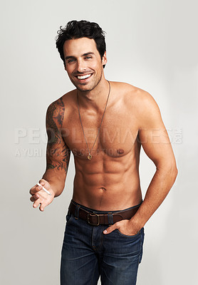 Buy stock photo A shirtless young man standing with his hand in his pocket and smoking