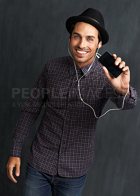 Buy stock photo Portrait of a hip young man listening to music and showing you his cellphone