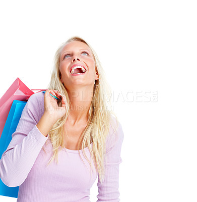 Buy stock photo Cheerful young woman holding colorful shopping bags looking upwards