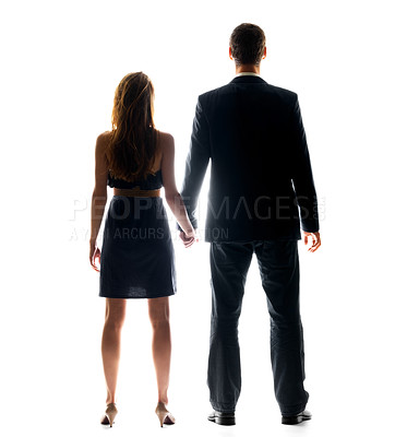 Buy stock photo Rear view of a young couple holding their hands while standing over bright background
