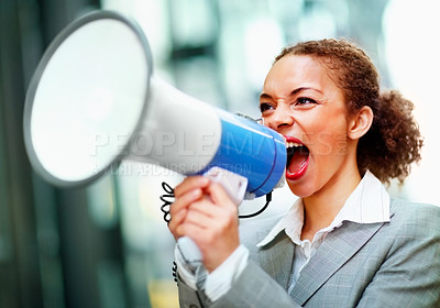 Buy stock photo Angry young African American business woman screaming into a megaphone