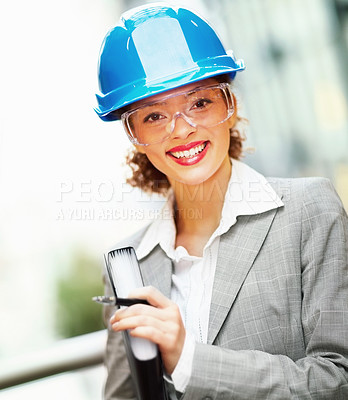 Buy stock photo Cute African American female architect holding a file, wearing a hardhat