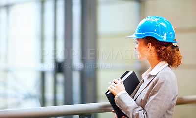 Buy stock photo Young female architect wearing a hardhat and holding a file folder, looking away