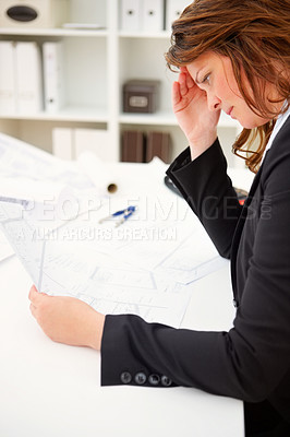 Buy stock photo Tensed mature business woman going through the blue prints at work