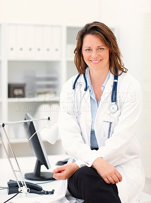 Buy stock photo Beautiful lady doctor smile while sitting in the clinic
