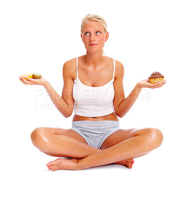 Buy stock photo An attractive woman deciding between sweets and fruits, isolated over white background
