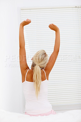 Buy stock photo Rear view of a young woman stretching her arms in bed