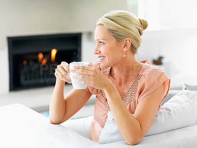 Buy stock photo Relaxed middle aged woman having a cup of coffee at home , looking away