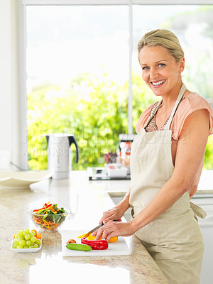 Buy stock photo Happy mature woman cutting vegetables for a salad