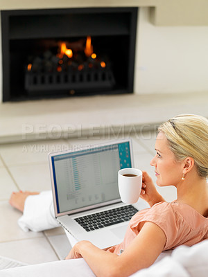 Buy stock photo Mature woman having coffee by a fireplace , warming herself while working on laptop