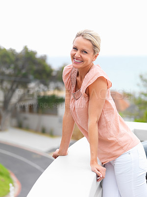 Buy stock photo A lovely middle aged woman smiling while standing besides the balcony