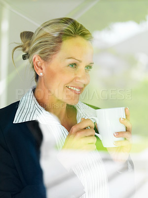 Buy stock photo Middle aged business woman having coffee while looking outside through window