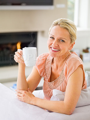 Buy stock photo Portrait of a relaxed middle aged woman having a cup of coffee at home