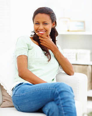 Buy stock photo Portrait of a smiling African American young woman sitting on couch at home