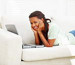 African American young woman lying on sofa and using laptop