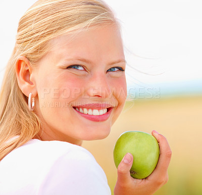 Buy stock photo Closeup portrait of a lovely young blond holding a green apple outdoors