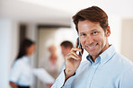 Happy businessman using mobile phone in office