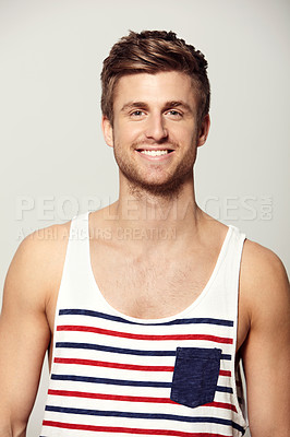 Buy stock photo Studio portrait of a handsome young man wearing a tank top and smiling at the camera