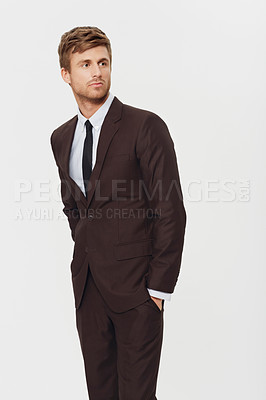 Buy stock photo Studio shot of a well-dressed handsome young businessman standing with his hands in his pockets