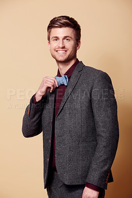 Buy stock photo Studio portrait of a stylishly-dressed young man holding his bow tie and smiling at the camera