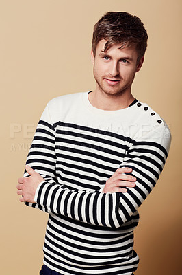 Buy stock photo Studio portrait of a stylishly-dressed young man standing with his arms crossed