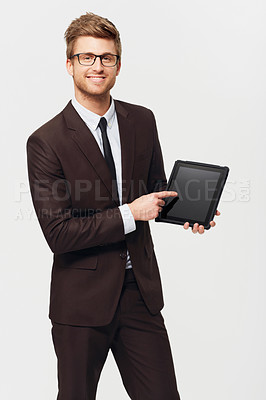 Buy stock photo Studio portrait of a stylishly-dressed young businessman pointing to a digital tablet he's holding