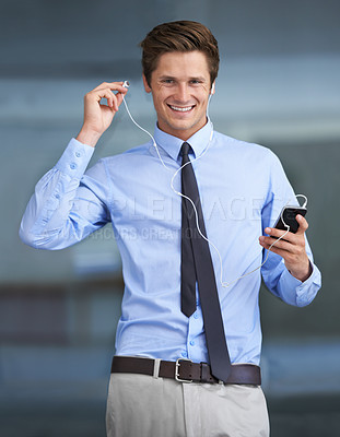 Buy stock photo Portrait of a handsome young businessman using his smartphone as an mp3 player