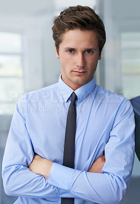 Buy stock photo A handsome young businessman crossing his arms and looking at you confidently