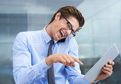 Buy stock photo An excited young businessman pointing at his tablet while taking a business call