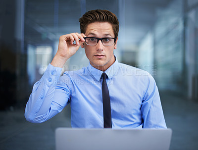 Buy stock photo A handsome young entrepreneur adjusting his glasses while working on his laptop