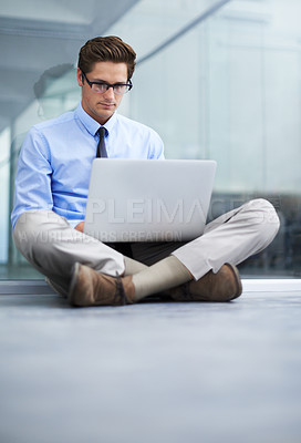 Buy stock photo A young businessman sitting on the floor of his empty office working on a laptop