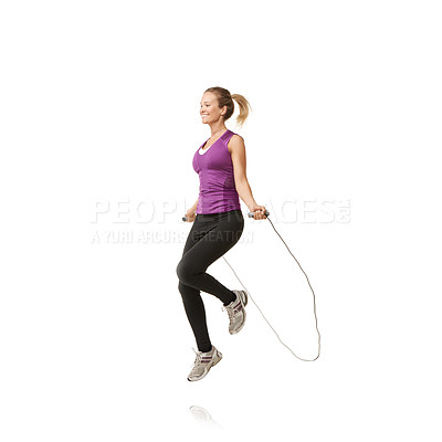 Buy stock photo An attractive young woman skipping against a white background