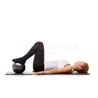 Buy stock photo A young woman using an exercise ball while lying on her exercise mat - isolated