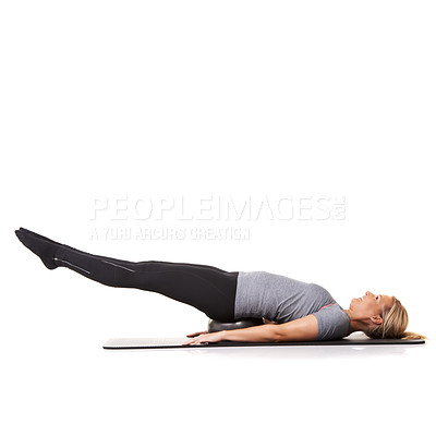 Buy stock photo A young woman lying on an exercise ball and extending her legs