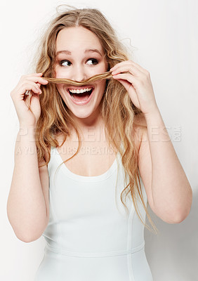 Buy stock photo Playful young woman making a mustache with her hair against a white background