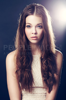 Buy stock photo A gorgeous young woman backlit with bright lights while isolated on black