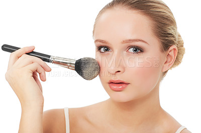 Buy stock photo A beautiful young woman applying blush to her cheeks while isolated on a white background