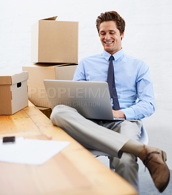 Buy stock photo A young businessman working on his laptop while surrounded by moving boxes