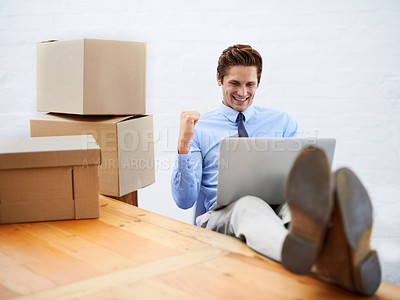 Buy stock photo A young businessman surrounded by moving boxes celebrating while using a laptop