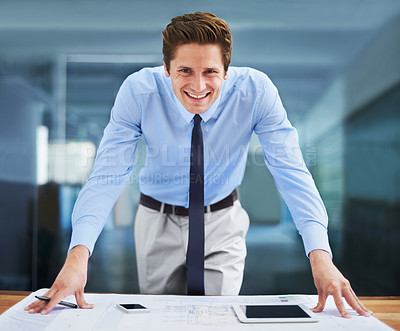 Buy stock photo Portrait of a successful young architect standing over his blueprints