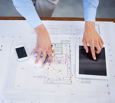 Buy stock photo Top view image of an architect using his tablet to perfect his blueprints