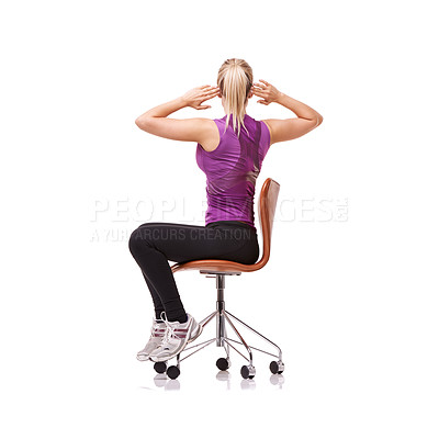 Buy stock photo Shot of a sporty woman doing stretches on a chair