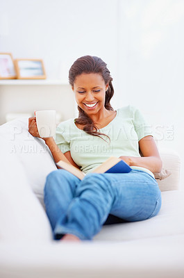 Buy stock photo Happy African American woman reading a book on the couch at tea time