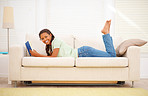 Cute young woman reading a book while relaxing on the sofa